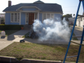 Satellite falls creating smoke in front of house Image
